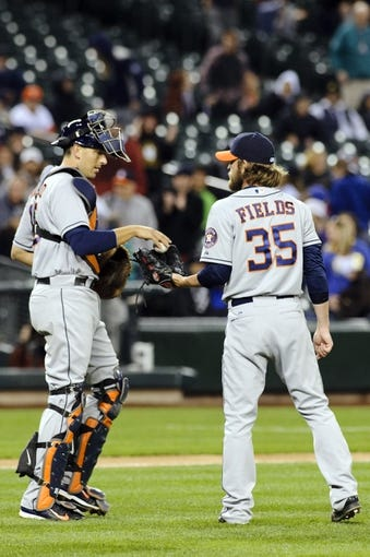 Apr 21, 2014; Seattle, WA, USA; Houston Astros catcher Jason Castro (15) hands the ball to relief pitcher Josh Fields (35) after the game against the Seattle Mariners at Safeco Field. Houston defeated Seattle 7-2. Mandatory Credit: Steven Bisig-USA TODAY Sports