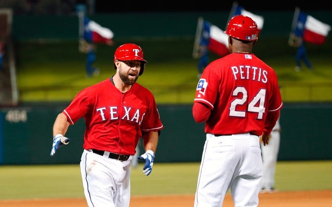 Apr 19, 2014; Arlington, TX, USA; Texas Rangers third baseman Kevin Kouzmanoff (6) celebrates with third base coach Gary Pettis (24) after hitting a home run during the game against the Chicago White Sox at Globe Life Park in Arlington. Texas won 6-3. Mandatory Credit: Kevin Jairaj-USA TODAY Sports