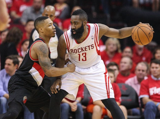 Apr 20, 2014; Houston, TX, USA; Houston Rockets guard James Harden (13) controls the ball during the second quarter as Portland Trail Blazers guard Damian Lillard (0) defends in game one during the first round of the 2014 NBA Playoffs at Toyota Center. Mandatory Credit: Troy Taormina-USA TODAY Sports