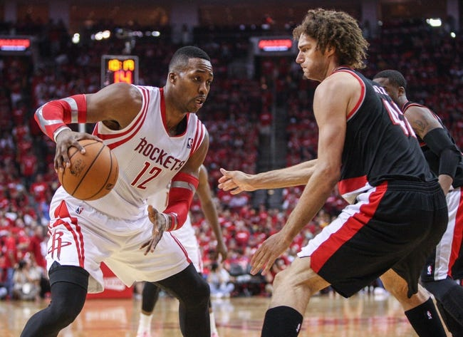 Apr 20, 2014; Houston, TX, USA; Houston Rockets center Dwight Howard (12) controls the ball during the third quarter as Portland Trail Blazers center Robin Lopez (42) defends in game one during the first round of the 2014 NBA Playoffs at Toyota Center. Mandatory Credit: Troy Taormina-USA TODAY Sports