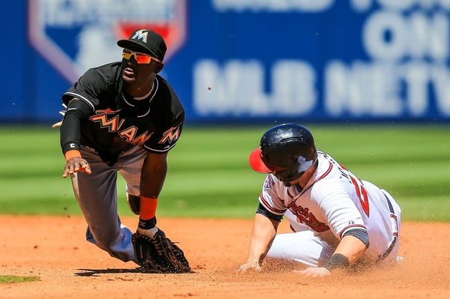 Apr 23, 2014; Atlanta, GA, USA; Atlanta Braves third baseman Chris Johnson (23) steals second on a wild pitch and throw on Miami Marlins shortstop Adeiny Hechavarria (3) in the fourth inning at Turner Field. Mandatory Credit: Daniel Shirey-USA TODAY Sports