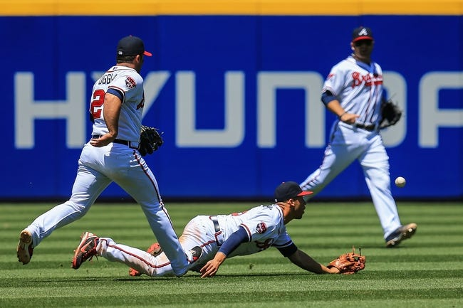 Apr 23, 2014; Atlanta, GA, USA; Atlanta Braves shortstop Andrelton Simmons (19) and second baseman Dan Uggla (26) attempt to catch a Miami Marlins right fielder Giancarlo Stanton (not pictured) RBI double  in the sixth inning at Turner Field. Mandatory Credit: Daniel Shirey-USA TODAY Sports