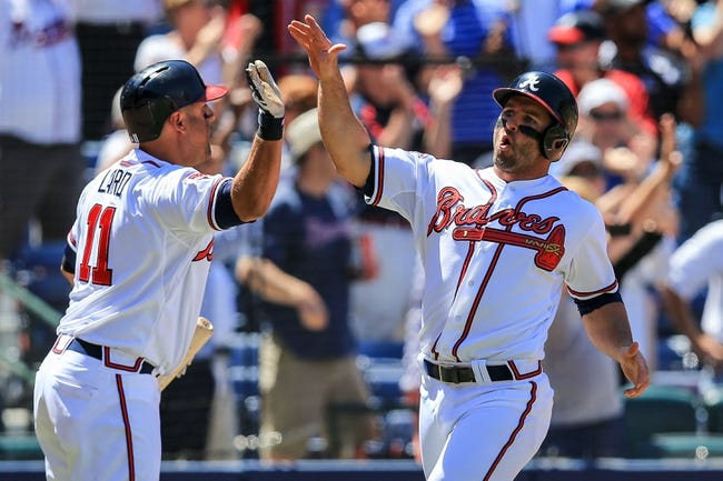 Apr 23, 2014; Atlanta, GA, USA; Atlanta Braves second baseman Dan Uggla (26) celebrates with catcher Gerald Laird (11) after scoring in the eighth inning against the Miami Marlins at Turner Field. Mandatory Credit: Daniel Shirey-USA TODAY Sports