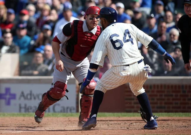 Apr 23, 2014; Chicago, IL, USA; Chicago Cubs outfielder Emilio Bonifacio (64) is tagged out by Arizona Diamondbacks catcher Miguel Montero (left) during the seventh inning of a baseball game at Wrigley Field. Mandatory Credit: Jerry Lai-USA TODAY Sports