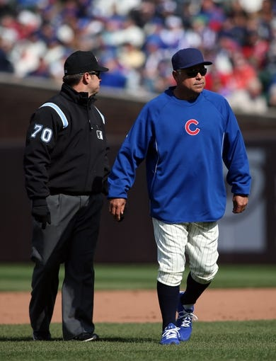 Apr 23, 2014; Chicago, IL, USA; Chicago Cubs manager Rick Renteria (right) talks with umpire D.J. Reyburn (70) during the ninth inning of a baseball game against the Arizona Diamondbacks at Wrigley Field. Mandatory Credit: Jerry Lai-USA TODAY Sports