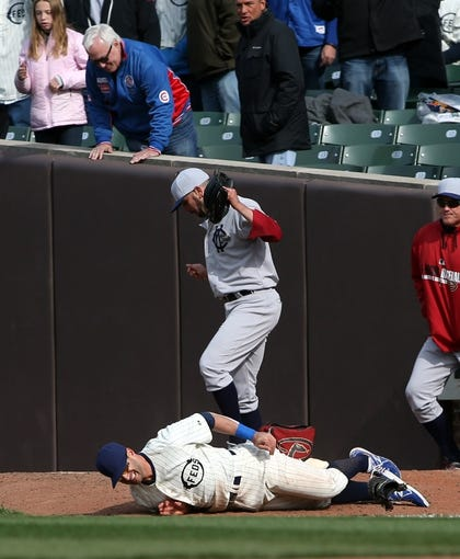 Apr 23, 2014; Chicago, IL, USA; Chicago Cubs outfielder Justin Ruggiano (bottom) reacts as he is injured while trying to catch a ball hit for a two-run triple by Arizona Diamondbacks second baseman Aaron Hill (not pictured) during the ninth inning of a baseball game at Wrigley Field. Mandatory Credit: Jerry Lai-USA TODAY Sports