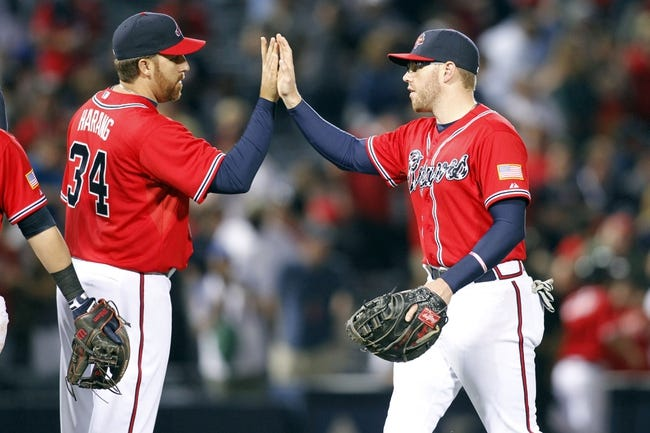Apr 26, 2014; Atlanta, GA, USA; Atlanta Braves starting pitcher Aaron Harang (34) celebrates a victory with first baseman Freddie Freeman (right) against the Cincinnati Reds in the ninth inning at Turner Field. The Braves defeated the Reds 4-1. Mandatory Credit: Brett Davis-USA TODAY Sports