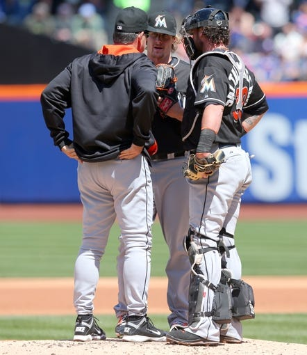 Apr 27, 2014; New York, NY, USA; Miami Marlins pitching coach Chuck Hernandez (left) talks with Miami Marlins starting pitcher Tom Koehler (34) and Miami Marlins catcher Jarrod Saltalamacchia (39) on the mound during the second inning of a game against the New York Mets at Citi Field. Mandatory Credit: Brad Penner-USA TODAY Sports