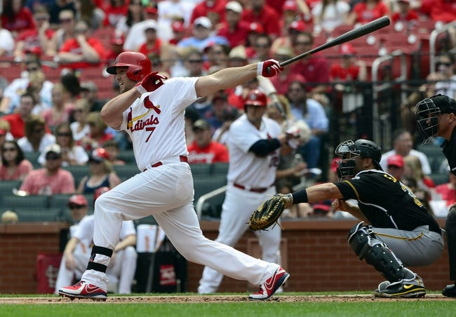 Apr 27, 2014; St. Louis, MO, USA; St. Louis Cardinals left fielder Matt Holliday (7) hits a one run sacrifice fly off of Pittsburgh Pirates starting pitcher Edinson Volquez (not pictured) during the first inning at Busch Stadium. Mandatory Credit: Jeff Curry-USA TODAY Sports