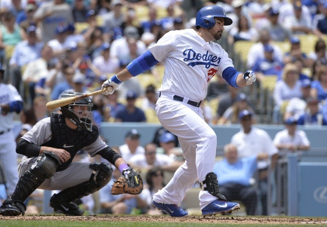 Apr 27, 2014; Los Angeles, CA, USA; Los Angeles Dodgers first baseman Adrian Gonzalez (23) singles to drive in Los Angeles Dodgers second baseman Dee Gordon (9) in the first inning against the Colorado Rockies at Dodger Stadium. Mandatory Credit: Robert Hanashiro-USA TODAY Sports