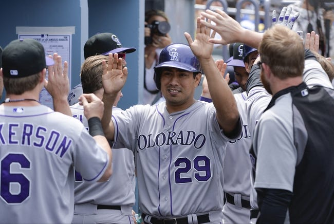 Apr 27, 2014; Los Angeles, CA, USA; Colorado Rockies starting pitcher Jorge De La Rosa (29) is greeted in the dugout after scoring on Colorado Rockies right fielder Brandon Barnes (1) hit in the second inning against the Los Angeles Dodgers at Dodger Stadium. Mandatory Credit: Robert Hanashiro-USA TODAY Sports