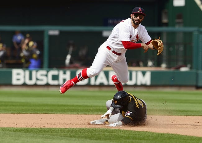 Apr 27, 2014; St. Louis, MO, USA; St. Louis Cardinals shortstop Daniel Descalso (33) leaps over Pittsburgh Pirates pinch hitter Josh Harrison (5) as he completes the double play during the eighth inning at Busch Stadium. St. Louis defeated Pittsburgh 7-0. Mandatory Credit: Jeff Curry-USA TODAY Sports