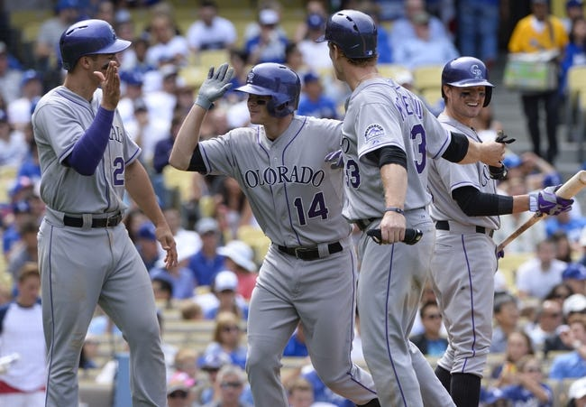 Apr 27, 2014; Los Angeles, CA, USA; Colorado Rockies second baseman Josh Rutledge (14) is congratulated at home by shortstop Troy Tulowitzki (2) and first baseman Justin Morneau (33) after hitting a 3-run homer in the sixth inning against the Los Angeles Dodgers at Dodger Stadium. Mandatory Credit: Robert Hanashiro-USA TODAY Sports