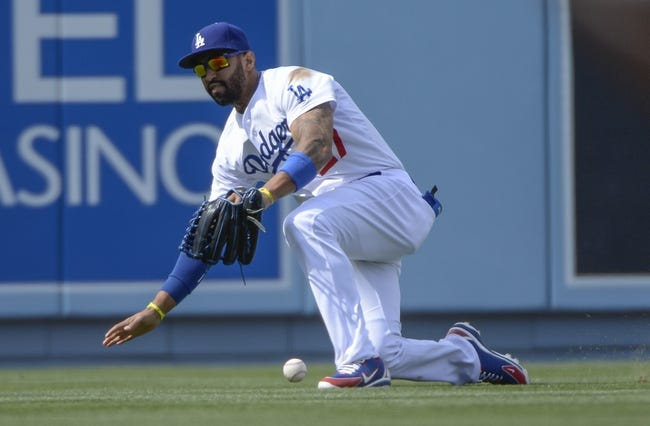 Apr 27, 2014; Los Angeles, CA, USA; Los Angeles Dodgers center fielder Matt Kemp (27) drops a fly ball of the bat of Colorado Rockies second baseman Josh Rutledge (14) in the eighth inning at Dodger Stadium. Kemp was charged with an error on the play. Mandatory Credit: Robert Hanashiro-USA TODAY Sports