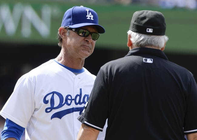 Apr 27, 2014; Los Angeles, CA, USA; Los Angeles Dodgers manager Don Mattingly (8) talks to first base umpire Stu Scheurwater after a close play at first base against the Colorado Rockies at Dodger Stadium. The play was reviewed and the call was overturned, the Rockies runner called out. Mandatory Credit: Robert Hanashiro-USA TODAY Sports
