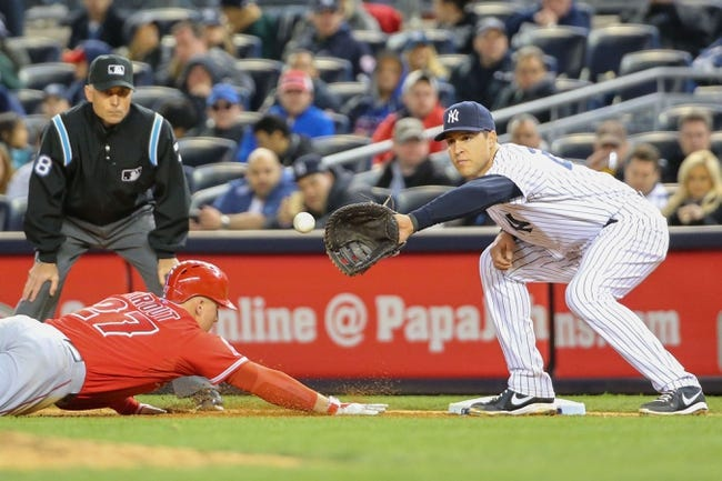 Apr 27, 2014; Bronx, NY, USA;  Los Angeles Angels center fielder Mike Trout (27) slides back to first as New York Yankees first baseman Mark Teixeira (25) waits for the ball during the seventh inningat Yankee Stadium. New York Yankees won 3-2.  Mandatory Credit: Anthony Gruppuso-USA TODAY Sports