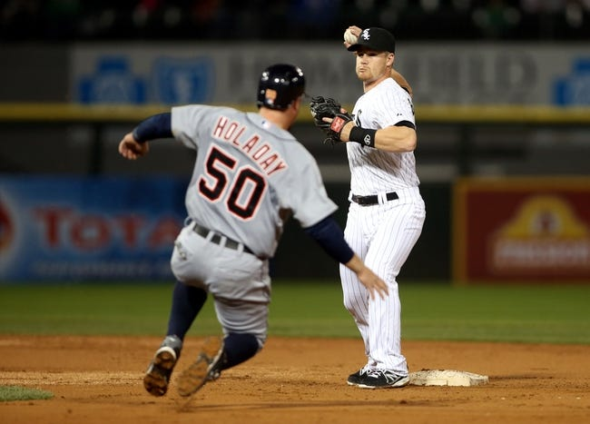Apr 29, 2014; Chicago, IL, USA; Chicago White Sox second baseman Gordon Beckham (right) turns a double play over Detroit Tigers catcher Bryan Holaday (50) in the third inning at U.S Cellular Field. Mandatory Credit: Jerry Lai-USA TODAY Sports