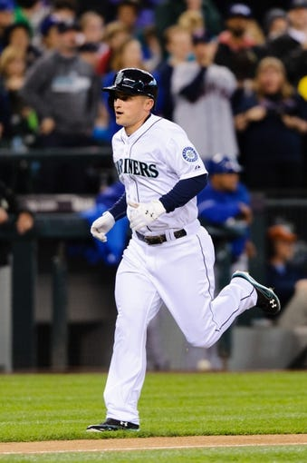 Apr 26, 2014; Seattle, WA, USA; Seattle Mariners third baseman Kyle Seager (15) scores a run after hitting a solo home run against the Texas Rangers at Safeco Field. Texas defeated Seattle 6-3. Mandatory Credit: Steven Bisig-USA TODAY Sports