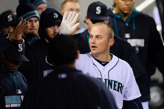 Apr 26, 2014; Seattle, WA, USA; Seattle Mariners third baseman Kyle Seager (15) celebrates with teammates in the dugout after hitting a solo home run against the Texas Rangers at Safeco Field. Texas defeated Seattle 6-3. Mandatory Credit: Steven Bisig-USA TODAY Sports