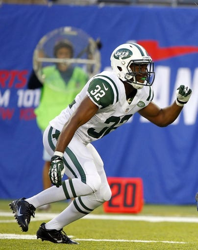 Aug 24, 2013; East Rutherford, NJ, USA; New York Giants cornerback returns punt during the first half  as New York Jets safety Josh Bush (32) closes in at MetLife Stadium. Mandatory Credit: Jim O'Connor-USA TODAY Sports