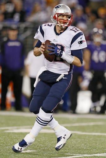 Dec 22, 2013; Baltimore, MD, USA; New England Patriots quarterback Tom Brady (12) drops back to pass against the Baltimore Ravens at M&T Bank Stadium. Mandatory Credit: Mitch Stringer-USA TODAY Sports