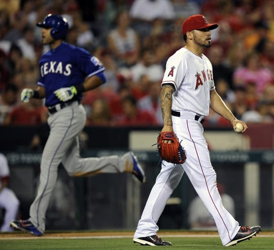 May 2, 2014; Anaheim, CA, USA; Los Angeles Angels starting pitcher Hector Santiago (right) reacts after allowing a two-run home run by Texas Rangers right fielder Alex Rios (left) during the sixth inning at Angel Stadium of Anaheim. Mandatory Credit: Kelvin Kuo-USA TODAY Sports
