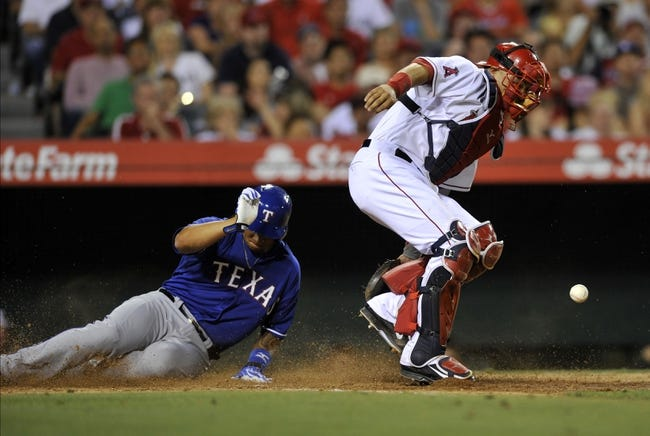 May 2, 2014; Anaheim, CA, USA; Texas Rangers designated hitter Michael Choice (back) slides in ahead of the throw to Los Angeles Angels catcher Hank Conger (front) for a score during the seventh inning at Angel Stadium of Anaheim. Mandatory Credit: Kelvin Kuo-USA TODAY Sports