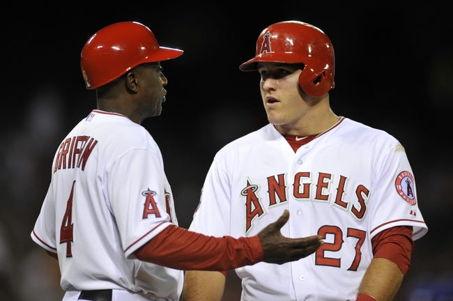 May 2, 2014; Anaheim, CA, USA; Los Angeles Angels first base coach Alfredo Griffin (left) talks with Los Angeles Angels center fielder Mike Trout (27) at first base against the Texas Rangers during the seventh inning at Angel Stadium of Anaheim. Mandatory Credit: Kelvin Kuo-USA TODAY Sports