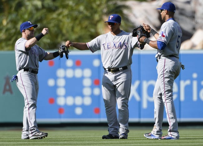 May 4, 2014; Anaheim, CA, USA; Texas Rangers left fielder Dan Robertson (19), center fielder Michael Choice (15) and right fielder Alex Rios (51) celebrate the Rangers 14-3 win over the Los Angeles Angels at Angel Stadium of Anaheim. Mandatory Credit: Robert Hanashiro-USA TODAY Sports