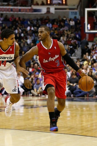 Dec 14, 2013; Washington, DC, USA; Los Angeles Clippers point guard Chris Paul (3) dribbles the ball as Washington Wizards shooting guard Glen Rice Jr. (14) defends at Verizon Center. Mandatory Credit: Geoff Burke-USA TODAY Sports