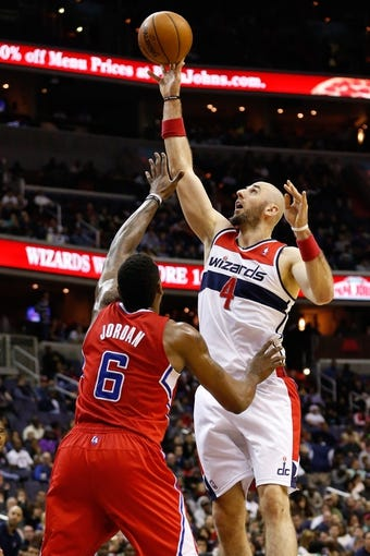 Dec 14, 2013; Washington, DC, USA; Washington Wizards center Marcin Gortat (4) shoots the ball over Los Angeles Clippers center DeAndre Jordan (6) at Verizon Center. Mandatory Credit: Geoff Burke-USA TODAY Sports