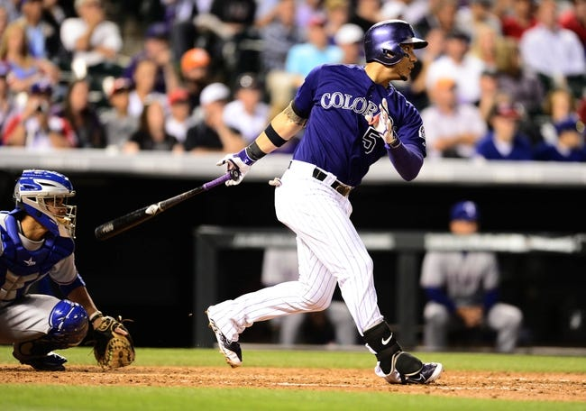 May 5, 2014; Denver, CO, USA; Colorado Rockies left fielder Carlos Gonzalez (5) hits a double in the fifth inning against the Texas Rangers at Coors Field. Mandatory Credit: Ron Chenoy-USA TODAY Sports