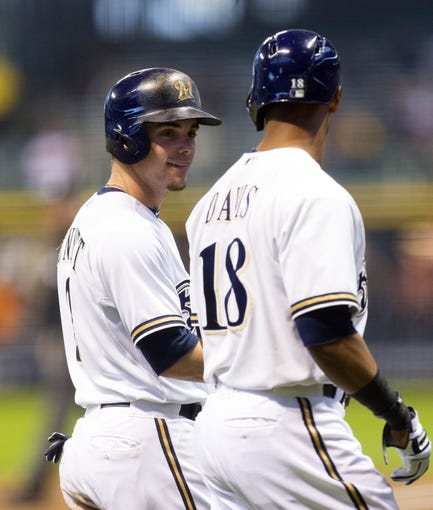May 6, 2014; Milwaukee, WI, USA; Milwaukee Brewers second baseman Scooter Gennett (2) talks with left fielder Khris Davis (18) after scoring a run during the first inning against the Arizona Diamondbacks at Miller Park. Mandatory Credit: Jeff Hanisch-USA TODAY Sports