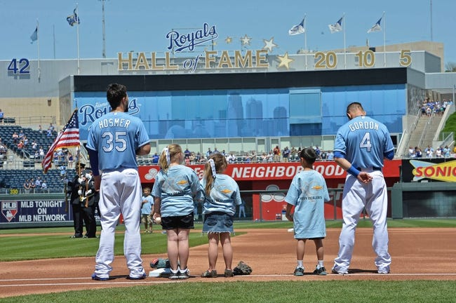 May 4, 2014; Kansas City, MO, USA; Kansas City Royals players Eric Hosmer (35) and Alex Gordon (4) stand with young fans during the National Anthem before a game against the Detroit Tigers at Kauffman Stadium. Mandatory Credit: Peter G. Aiken-USA TODAY Sports
