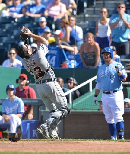 May 4, 2014; Kansas City, MO, USA; Detroit Tigers catcher Alex Avila (13) catches the final out of the game, as Kansas City Royals player Billy Butler (16) looks on during the ninth inning at Kauffman Stadium. The Tigers beat the Royals 9-4. Mandatory Credit: Peter G. Aiken-USA TODAY Sports