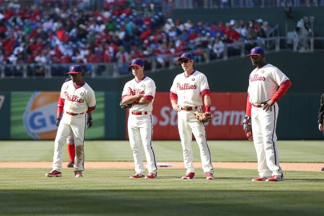 May 4, 2014; Philadelphia, PA, USA; Philadelphia Phillies shortstop Jimmy Rollins (11) and third baseman Jayson Nix (7) and second baseman Chase Utley (26) and first baseman Ryan Howard (6) watch on as relief pitcher Antonio Bastardo (not pictured) warms up during a game against the Washington Nationals at Citizens Bank Park. The Phillies defeated the Nationals 1-0.  Mandatory Credit: Bill Streicher-USA TODAY Sports