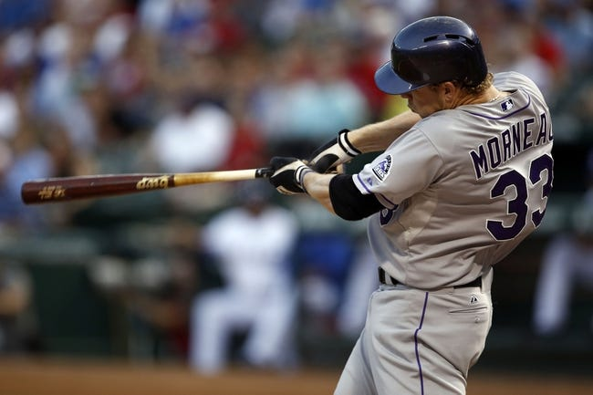 May 7, 2014; Arlington, TX, USA; Colorado Rockies first baseman Justin Morneau (33) follows through on his swing for a single against the Texas Rangers during the fourth inning of a baseball game at Globe Life Park in Arlington. Mandatory Credit: Jim Cowsert-USA TODAY Sports