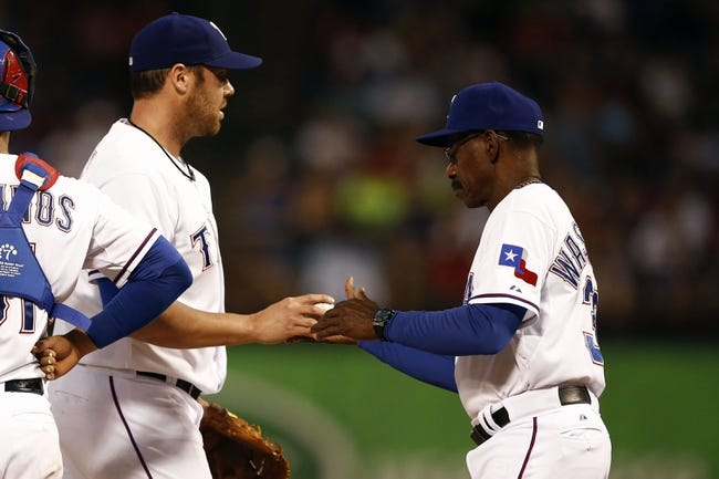 May 7, 2014; Arlington, TX, USA; Texas Rangers starting pitcher Colby Lewis (48) hands the ball over to manager Ron Washington (38) during the fourth inning of a baseball game against the Colorado Rockies at Globe Life Park in Arlington. Mandatory Credit: Jim Cowsert-USA TODAY Sports