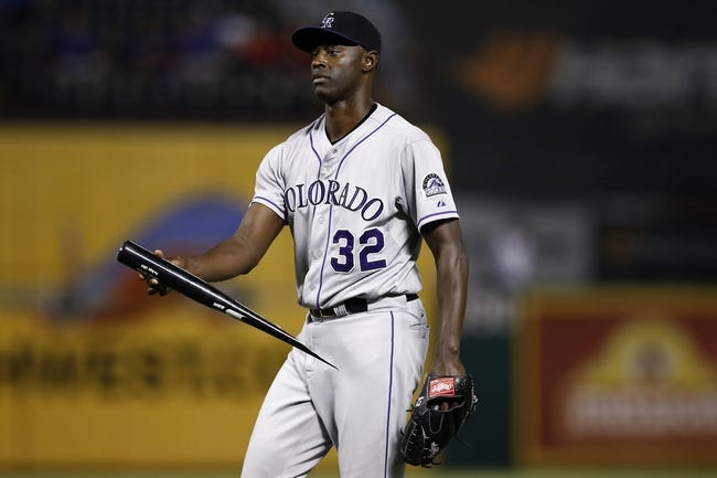 May 7, 2014; Arlington, TX, USA; Colorado Rockies relief pitcher LaTroy Hawkins (32) picks up the broken bat of Texas Rangers center fielder Leonys Martin (not pictured) during the ninth inning of a baseball game at Globe Life Park in Arlington. The Rockies won 9-2. Mandatory Credit: Jim Cowsert-USA TODAY Sports