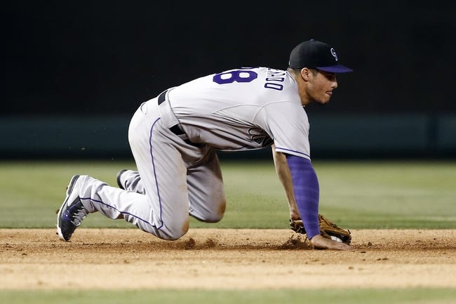 May 7, 2014; Arlington, TX, USA; Colorado Rockies third baseman Nolan Arenado (28) fields the ground-out hit by Texas Rangers right fielder Alex Rios (not pictured) during the ninth inning of a baseball game at Globe Life Park in Arlington. The Rockies won 9-2. Mandatory Credit: Jim Cowsert-USA TODAY Sports