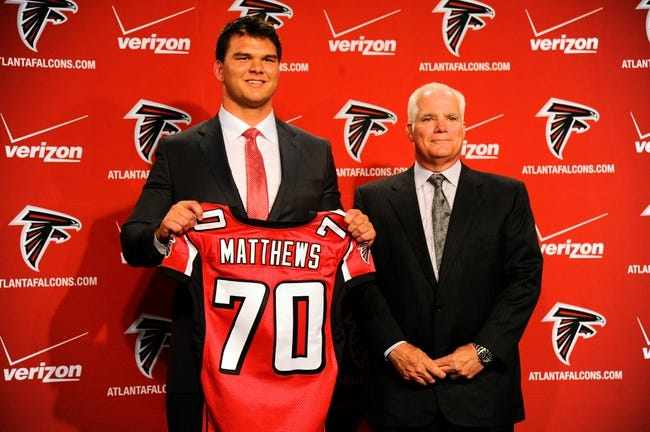 May 9, 2014; Atlanta, GA, USA; Atlanta Falcons head coach Mike Smith and first round draft pick tackle Jake Matthews (with jersey) shown during a press conference at Falcons Training Facility. Mandatory Credit: Dale Zanine-USA TODAY Sports