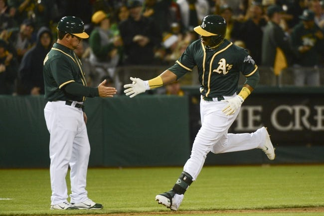 May 9, 2014; Oakland, CA, USA; Oakland Athletics left fielder Yoenis Cespedes (52, right) is congratulated by third base coach Mike Gallego (2, left) for hitting a solo home run against the Washington Nationals during the fifth inning at O.co Coliseum. Mandatory Credit: Kyle Terada-USA TODAY Sports
