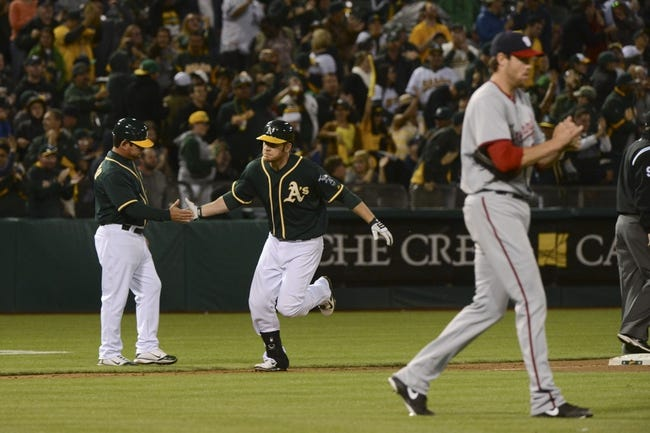 May 9, 2014; Oakland, CA, USA; Oakland Athletics first baseman Brandon Moss (37, center) is congratulated by third base coach Mike Gallego (2, left) for hitting a two-run home run off of Washington Nationals starting pitcher Doug Fister (58, right) during the fifth inning at O.co Coliseum. Mandatory Credit: Kyle Terada-USA TODAY Sports
