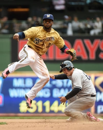 May 11, 2014; Milwaukee, WI, USA; Milwaukee Brewers second baseman Rickie Weeks (23) completes a double play after forcing out New York Yankees catcher John Ryan Murphy (66) in the eighth inning at Miller Park. Mandatory Credit: Benny Sieu-USA TODAY Sports