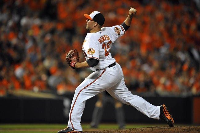 May 13, 2014; Baltimore, MD, USA; Baltimore Orioles pitcher Tommy Hunter (29) pitches in the ninth inning against the Detroit Tigers at Oriole Park at Camden Yards. The Tigers defeated the Orioles 4-1. Mandatory Credit: Joy R. Absalon-USA TODAY Sports