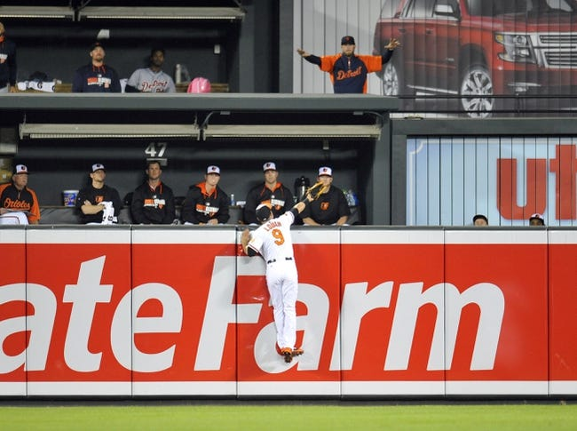 May 13, 2014; Baltimore, MD, USA; Baltimore Orioles left fielder David Lough (9) cannot catch a three-run home ball hit by Detroit Tigers first baseman Miguel Cabrera (not shown) in the ninth inning at Oriole Park at Camden Yards. The Tigers defeated the Orioles 4-1. Mandatory Credit: Joy R. Absalon-USA TODAY Sports