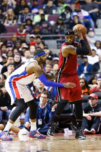 Mar 28, 2014; Auburn Hills, MI, USA; Miami Heat forward LeBron James (6) dribbles around Detroit Pistons forward Josh Smith (6) in the third quarter at The Palace of Auburn Hills. Miami won 110-78. Mandatory Credit: Rick Osentoski-USA TODAY Sports