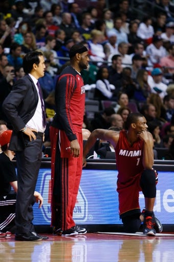 Mar 28, 2014; Auburn Hills, MI, USA; Miami Heat head coach Erik Spoelstra (left) forward LeBron James (6) and center Chris Bosh (1) on the sideline against the Detroit Pistons at The Palace of Auburn Hills. Mandatory Credit: Rick Osentoski-USA TODAY Sports
