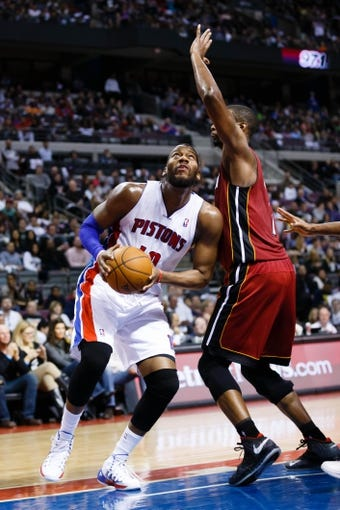 Mar 28, 2014; Auburn Hills, MI, USA; Detroit Pistons forward Greg Monroe (10) dribbles around Miami Heat center Chris Bosh (1) in the second half at The Palace of Auburn Hills. Miami won 110-78. Mandatory Credit: Rick Osentoski-USA TODAY Sports