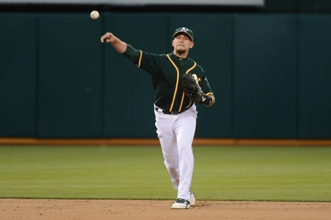 May 10, 2014; Oakland, CA, USA; Oakland Athletics shortstop Jed Lowrie (8) throws the baseball to first base against the Washington Nationals during the eighth inning at O.co Coliseum. The Athletics defeated the Nationals 4-3 in 10 innings. Mandatory Credit: Kyle Terada-USA TODAY Sports